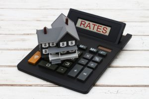 Calculating your interest rates, A gray model house on a calculator with word Rates over a distressed wood background